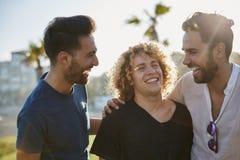 3 мужских друз стоя совместно смеяться над снаружи Стоковые Фотографии RF