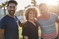 3 мужских друз стоя совместно снаружи в солнечном свете Стоковые Изображения