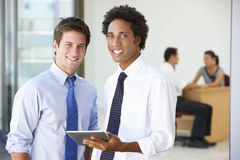 2 мужских исполнительной власти используя планшет с встречей офиса в предпосылке Стоковое Изображение RF