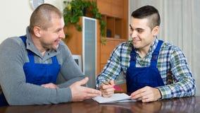 2 мужских работника читая документы Стоковое Изображение