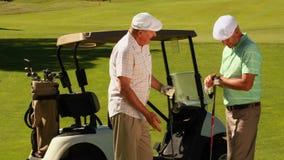 2 мужских друз беседуя на поле для гольфа их kart видеоматериал