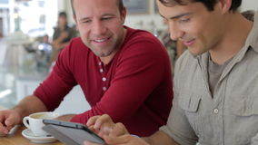 2 мужских друз в кофейне смотря таблетку цифров сток-видео
