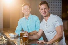 2 мужских друз имея пиво на счетчике бара Стоковая Фотография