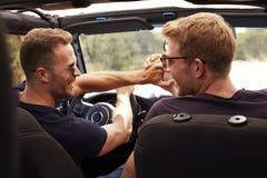 2 мужских друз управляя открытым верхним автомобилем на проселочной дороге Стоковое Фото
