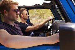 2 мужских друз управляя открытым верхним автомобилем на проселочной дороге Стоковое Изображение RF