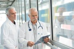 2 мужских старших доктора с доской сзажимом для бумаги на коридоре больницы Стоковые Фото