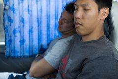 2 мужских туристских пассажира спать на автобусе стоковое фото rf