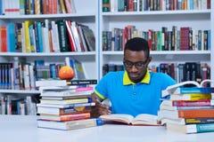Мужское Афро-американское чтение студента колледжа в библиотеке стоковое фото