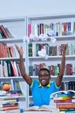 Мужское Афро-американское чтение студента колледжа в библиотеке стоковые фотографии rf