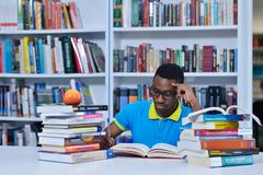 Мужское Афро-американское чтение студента колледжа в библиотеке стоковые изображения rf