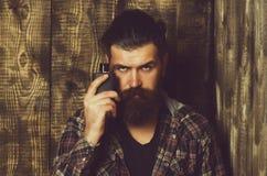 Мужское благоухание и парфюмерия Косметика Бородатый человек представляя с черной бутылкой дух или кёльна стоковое фото
