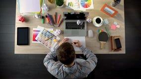 Мужское дизайнерское сочинительство на бумажных идеях и планах сидя в его офисе, творческих способностях стоковая фотография