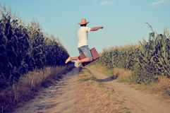 Мужское летание или скакать с чемоданом на стране Стоковые Фотографии RF