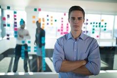 Мужское исполнительное положение в офисе с коллегами в предпосылке Стоковое Фото