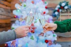 2 мужское и женские руки держа шампанское на предпосылке рождественской елки indoors Стоковые Изображения RF