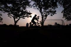 Мужское катание велосипедиста вокруг футбольного поля Стоковые Изображения