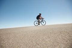 Мужское катание велосипедиста на плоской дороге против голубого неба Стоковое Фото