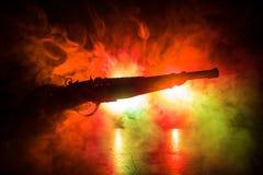 Мужское оружие удерживания руки на черной предпосылке с дымом тонизировало задние света Силуэт оружия в руке Концепция преступлен стоковое фото rf