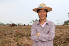 Мужское положение фермера и комод обнимать в ферме кассавы стоковая фотография