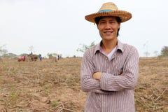 Мужское положение фермера и комод обнимать в ферме кассавы стоковое изображение