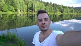 Мужское принимая фото около красивого ландшафта, лес selfie около озера сток-видео