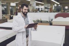 Мужское протезное представление на фоне большого магазина кроватей Он держит таблетку в его руках и смотрит его стоковые изображения