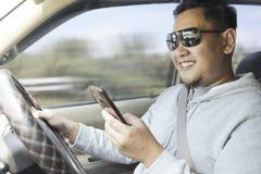 Мужское сообщение чтения водителя по умному телефону пока управляющ автомобилем стоковая фотография rf