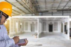 Мужское сочинительство осмотра инженера в фабрике с примечанием на блокноте Стоковое Изображение RF
