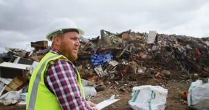 Мужское сочинительство работника на доске сзажимом для бумаги в junkyard 4k видеоматериал