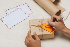 Мужское сочинительство руки на бирке багажа на пакете коричневой бумаги Стоковое фото RF