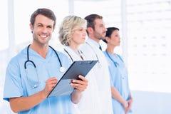 Мужское сочинительство доктора сообщает с коллегами в медицинском офисе Стоковая Фотография RF