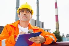 Мужское сочинительство рабочий-строителя на доске сзажимом для бумаги на индустрии Стоковое фото RF