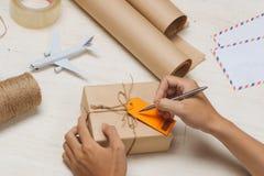 Мужское сочинительство руки на бирке багажа на пакете коричневой бумаги Стоковое Изображение RF