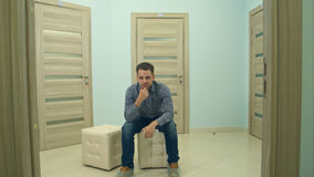 Мужское терпеливое ждать назначение ` s доктора кивая его головой и смотря в камеру Стоковое Фото