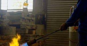 Мужское топление работника отливает в форму в мастерской 4k акции видеоматериалы