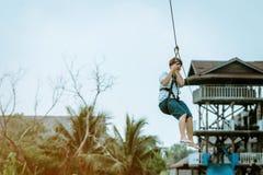 Мужское туристское летание на лисе летания zipline aka через озеро на рынке Паттайя плавая, стоковое фото