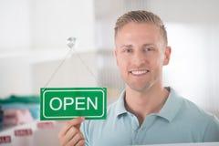 Мужское удерживание предпринимателя открытое подписывает внутри магазин одежды Стоковое фото RF