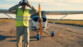 Мужской авиатор идет далеко от самолета и принимать наушники видеоматериал