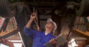 Мужской автоматический механик проверяет путь undercarriage автомобиля в гараже акции видеоматериалы
