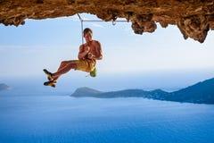 Мужской альпинист на свисая своде утеса, красивом виде побережья b Стоковые Фото