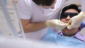 Мужской дантист делает прессформу передних зубов пациента используя желтую массу акции видеоматериалы