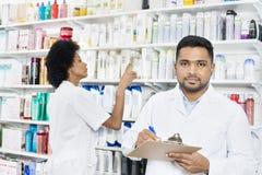 Мужской аптекарь держа доску сзажимом для бумаги пока коллега аранжируя Stoc стоковые фото