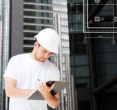 Мужской архитектор в шлеме смотря светокопию Стоковые Изображения RF