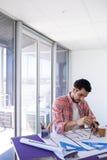 Мужской архитектор работая на светокопии над чертя таблицей Стоковое Изображение