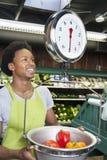 Мужской Афро-американский товаровед веся болгарские перцы на масштабе стоковая фотография rf
