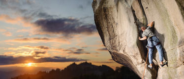 Мужской альпинист взбираясь большой валун в природе с веревочкой Стоковое фото RF