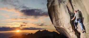 Мужской альпинист взбираясь большой валун в природе с веревочкой Стоковые Фотографии RF