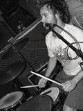 Мужской барабанщик вокалиста утеса поя близко к стойке микрофона играя барабанчики в черно-белом стоковые изображения