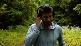 Мужской бегун в теплых одеждах в парке осени слушая к музыке и одеждам клобука видеоматериал