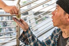 Мужской бездомный попрошайка получая монетку bitcoin золота стоковые изображения rf